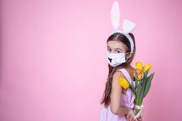 Menina com orelhas de coelho da páscoa e usando uma máscara facial com um buquê de tulipas nas mãos em uma rosa Foto gratuita