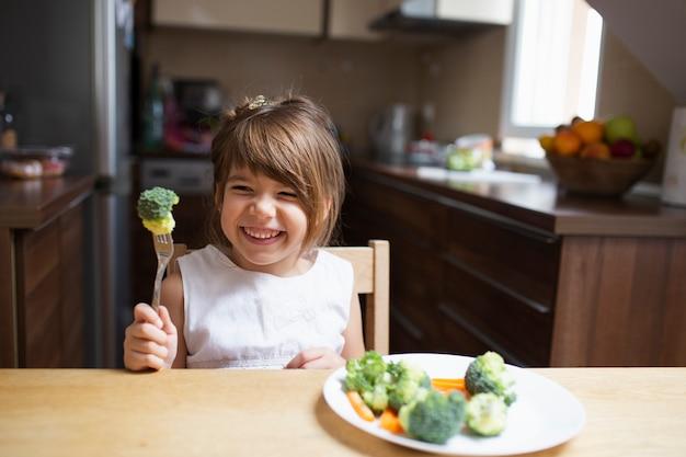 Menina com os olhos fechados comendo legumes Foto gratuita
