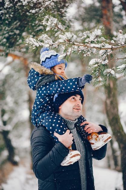 Menina com os pais brincando em um parque de inverno Foto gratuita