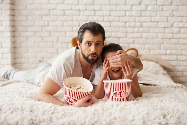 Menina com pai assistir filme assustador e comer pipoca. Foto Premium