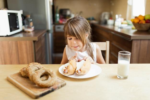 Menina com pastelaria e leite em casa Foto gratuita