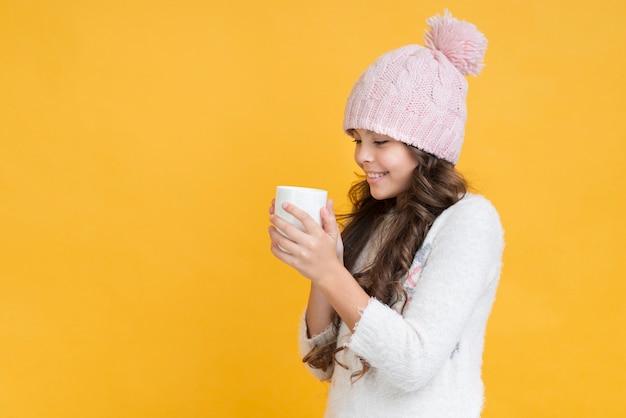 Menina com roupas de inverno e um copo nas mãos Foto gratuita