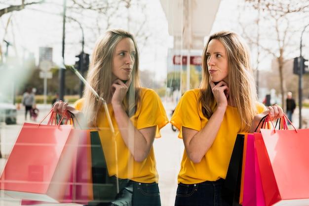 Menina com sacolas de compras, olhando para o seu reflexo Foto gratuita