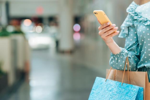 Menina com sacos de compras com fundo desfocado Foto gratuita