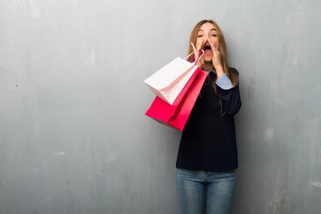 Menina com sacos de compras gritando e anunciando algo Foto Premium