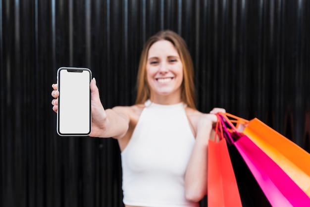 Menina com sacos de compras, segurando o modelo de telefone Foto gratuita