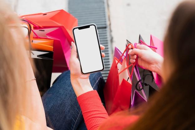 Menina com sacos de compras, segurando o telefone Foto gratuita
