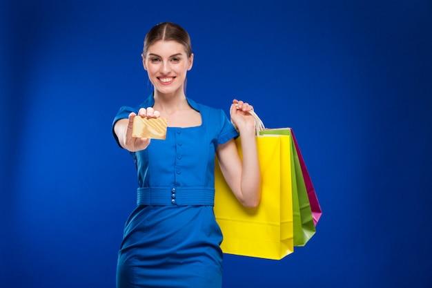 Menina com sacos e cartão de crédito nas mãos Foto Premium