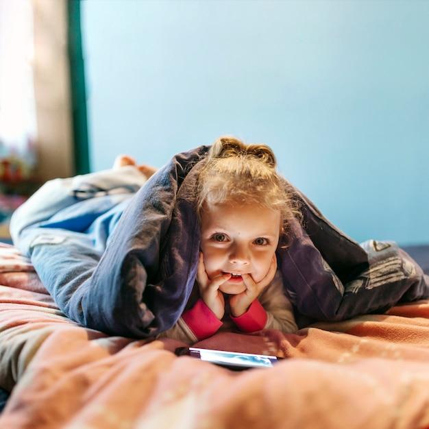 Menina, com, smartphone, olhando câmera Foto gratuita