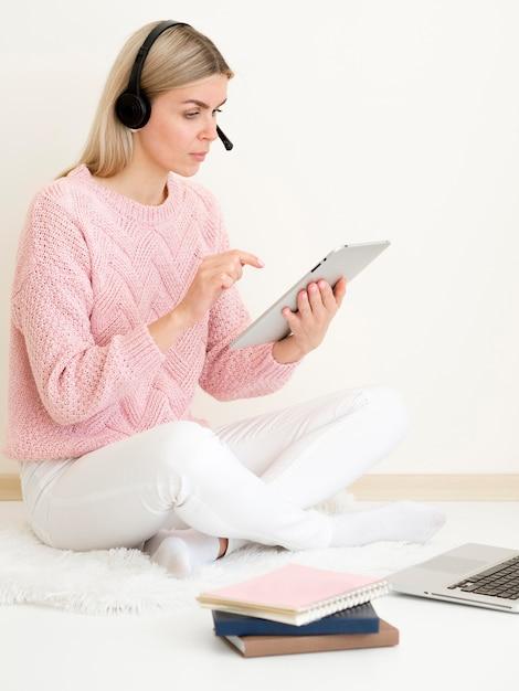 Menina com suéter rosa trabalhando em tablet digital Foto gratuita