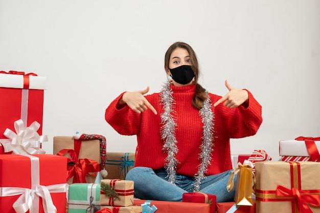 Menina com suéter vermelho apontando com o dedo ela mesma sentada e apresentando uma máscara preta sobre branco Foto gratuita