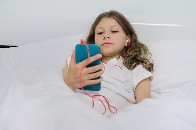 Menina com telefone celular em fones de ouvido, sentado na cama branca em casa Foto Premium
