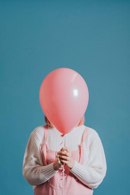 Menina com um balão de hélio rosa Foto gratuita
