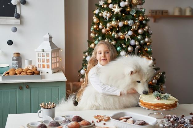 Menina com um cachorro perto da árvore de natal no natal Foto Premium