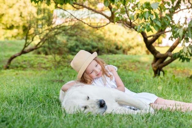Menina com um cão branco grande no parque. uma menina de 5 anos linda no vestido branco abraça seu cachorro favorito durante uma caminhada de verão. Foto Premium