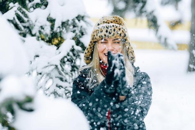 Menina com um chapéu de inverno elegante com uma estampa de leopardo se alegra na neve Foto Premium