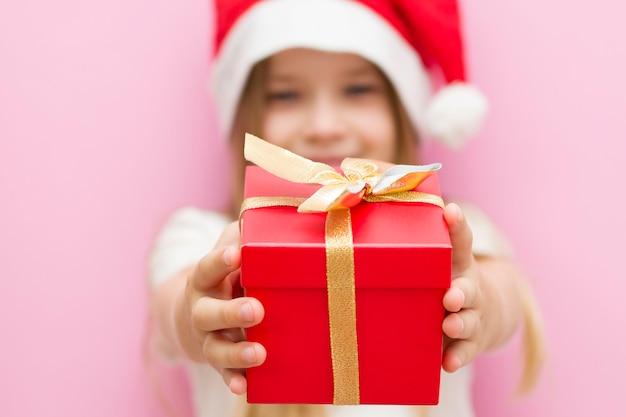 Menina com um chapéu vermelho de natal apresenta uma caixa vermelha com um laço de ouro, um presente. sorri. o novo ano é 2021. close up Foto Premium