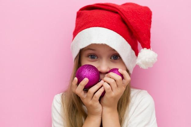 Menina com um chapéu vermelho de natal tem balões rosa de natal nas mãos. fechar-se. feliz ano novo 2021 Foto Premium