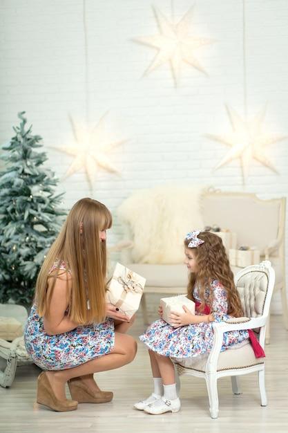 Menina com um grande presente de natal, juntamente com a mãe posa perto da árvore de natal. Foto Premium