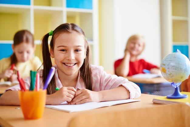 Menina com um grande sorriso em uma sala de aula Foto gratuita