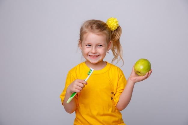 Menina com uma escova de dentes, menina com uma escova de dentes e uma maçã. Foto Premium