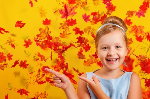 Menina com uma fantasia de princesa em um fundo de folhas de outono caindo Foto Premium
