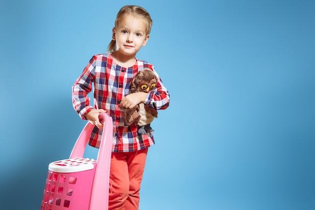 Menina com uma mala e um brinquedo favorito sobre um fundo azul. conceito de viagens Foto Premium