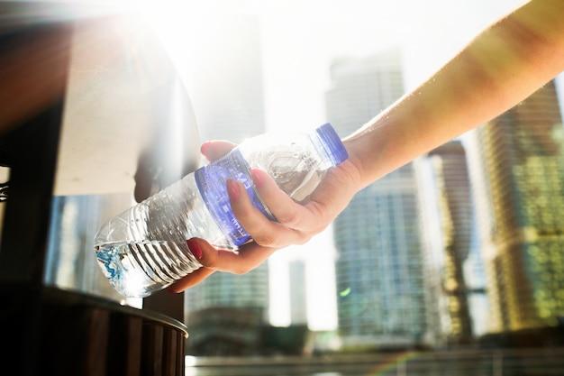 Menina com unhas vermelhas coloca uma garrafa de água com scrapheap Foto Premium