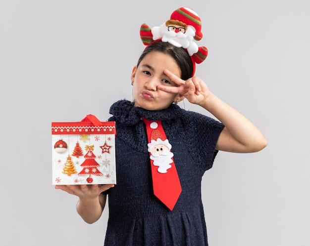 Menina com vestido de malha usando gravata vermelha com aro de natal engraçado na cabeça segurando um presente de natal feliz e alegre olhando mostrando o sinal de v Foto gratuita