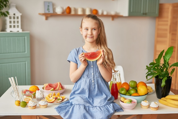 Menina come frutas na cozinha Foto Premium