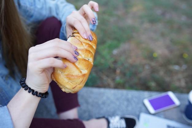 Menina come pão com chocolate na rua Foto Premium