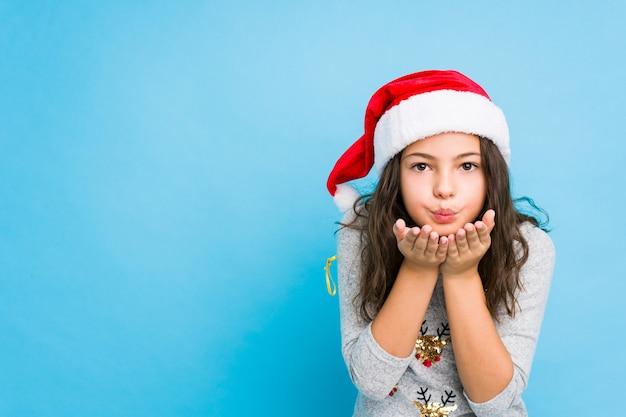 Menina comemorando o dia de natal, dobrar os lábios e segurando as palmas das mãos para enviar beijo de ar. Foto Premium