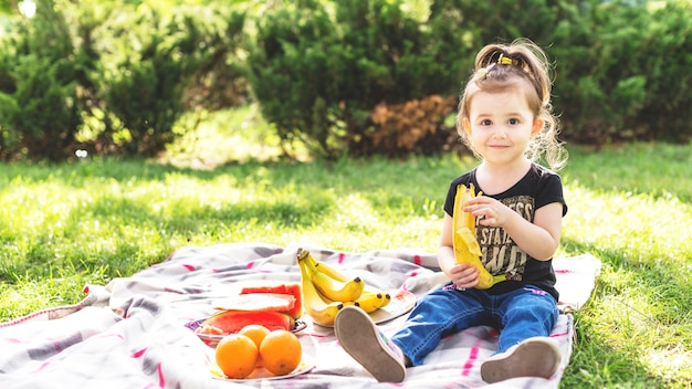 Menina comendo banana no piquenique no parque Foto gratuita