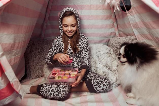 Menina comendo doces em uma barraca dentro de casa e um cachorro Foto gratuita