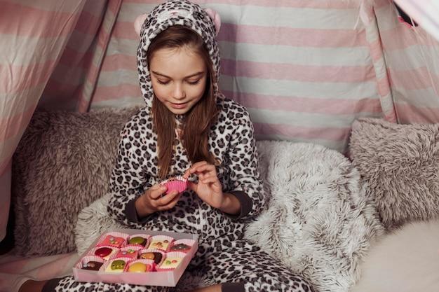 Menina comendo doces em uma barraca dentro de casa Foto gratuita