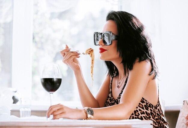 Menina comendo macarrão em um restaurante, bebendo seu vinho tinto Foto Premium