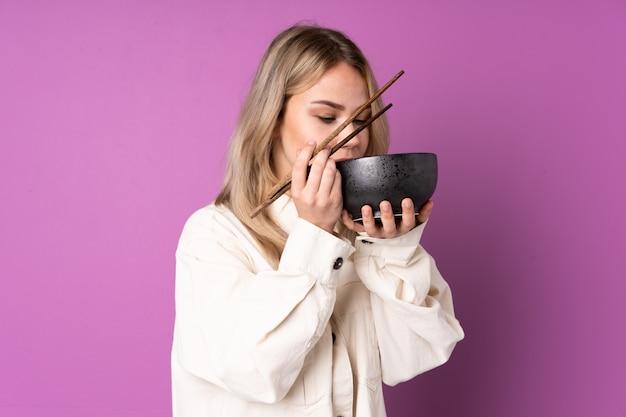 Menina comendo macarrão na parede roxa Foto Premium