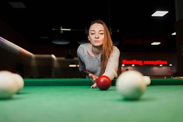 Menina concentrada enquanto estiver jogando bilhar Foto Premium