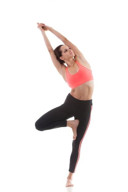 Menina concentrada mostrando um exercício de equilíbrio Foto gratuita