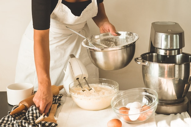 Menina confeiteiro está preparando um bolo Foto Premium