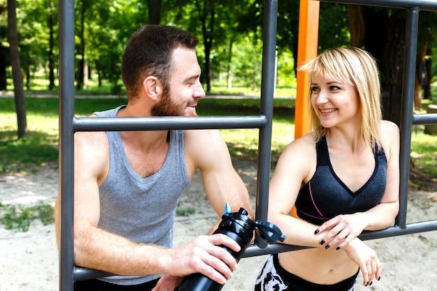 Menina consideravelmente loura e homem farpado que descansam após o treinamento do exercício em um parque ao ar livre. Foto Premium