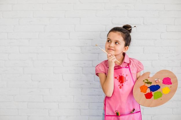 Menina contemplada segurando a paleta e o pincel na mão de pé perto da parede branca Foto gratuita