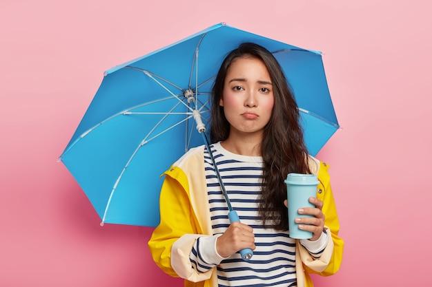 Menina coreana triste e chateada sob o guarda-chuva no outono chuvoso, bebe café para viagem, vestida com capa de chuva à prova d'água Foto gratuita