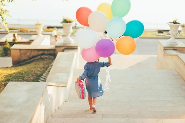 Menina correndo nas escadas segurando balões coloridos e mala infantil Foto gratuita