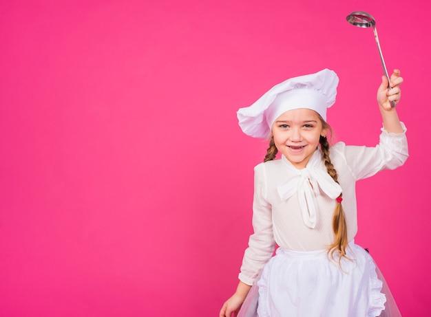 Menina cozinhar com concha sorridente Foto gratuita