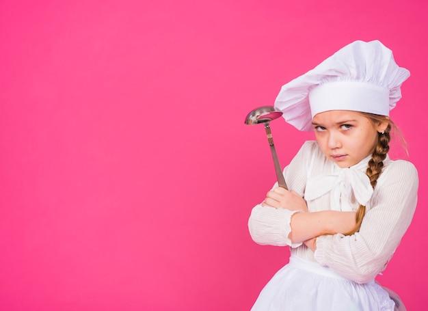 Menina cozinhar com concha travessia de braços Foto gratuita