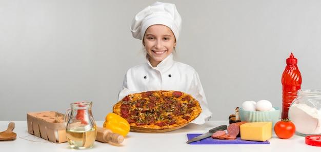 Menina-cozinhar com pizza nas mãos Foto Premium