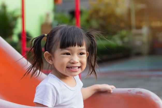 Menina criança asiática feliz sorrindo e rindo. ela brincando com o brinquedo da barra deslizante no playground. aprendizagem e ativa do conceito de crianças. Foto Premium