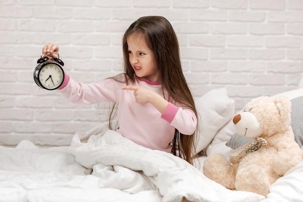Menina criança de pijama com relógio Foto Premium
