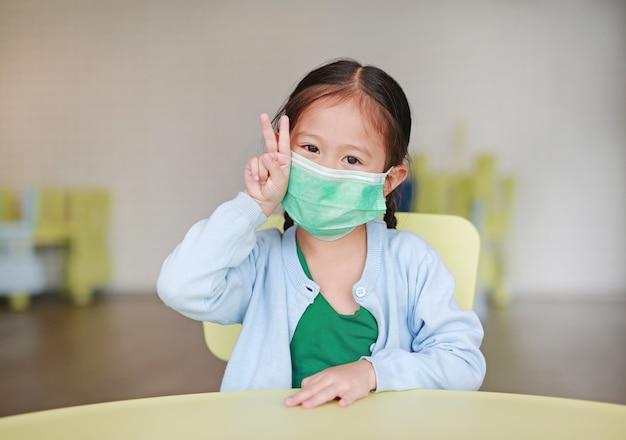 Menina criança, desgastar, um, máscara protetora, com, mostrando, dois dedos Foto Premium